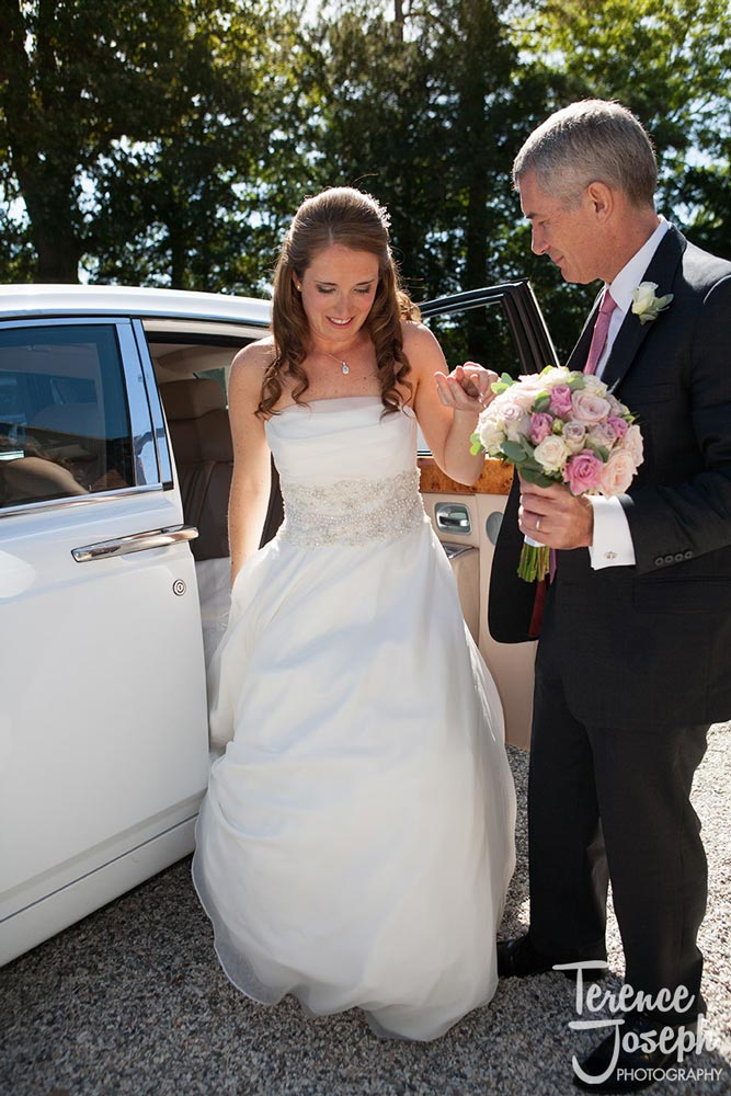 The father of the bride helps her daughter out of the wedding car