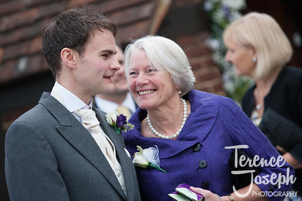 Happy mum looks at her son at wedding in Reading