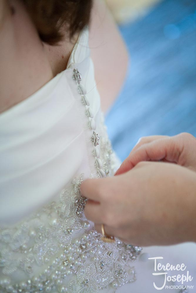 Sister buttoning the bride's wedding dress for her Reading Wedding