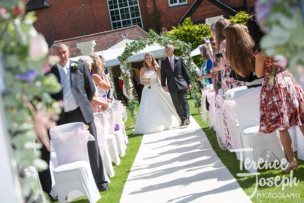 The bride and father walk down the aisle at Trunkwell House