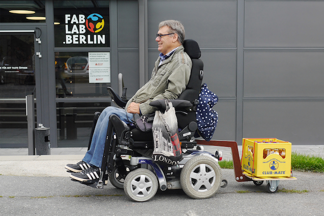 Wheelchair user with a trailer carrying a beverage crate