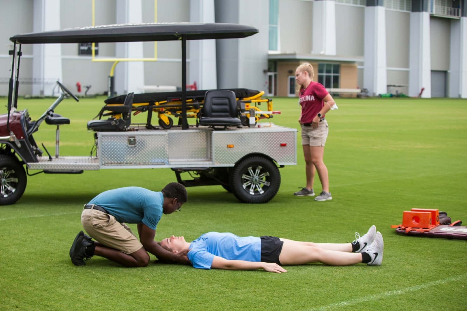 Athletic Trainer On the Field With Injured Athlete
