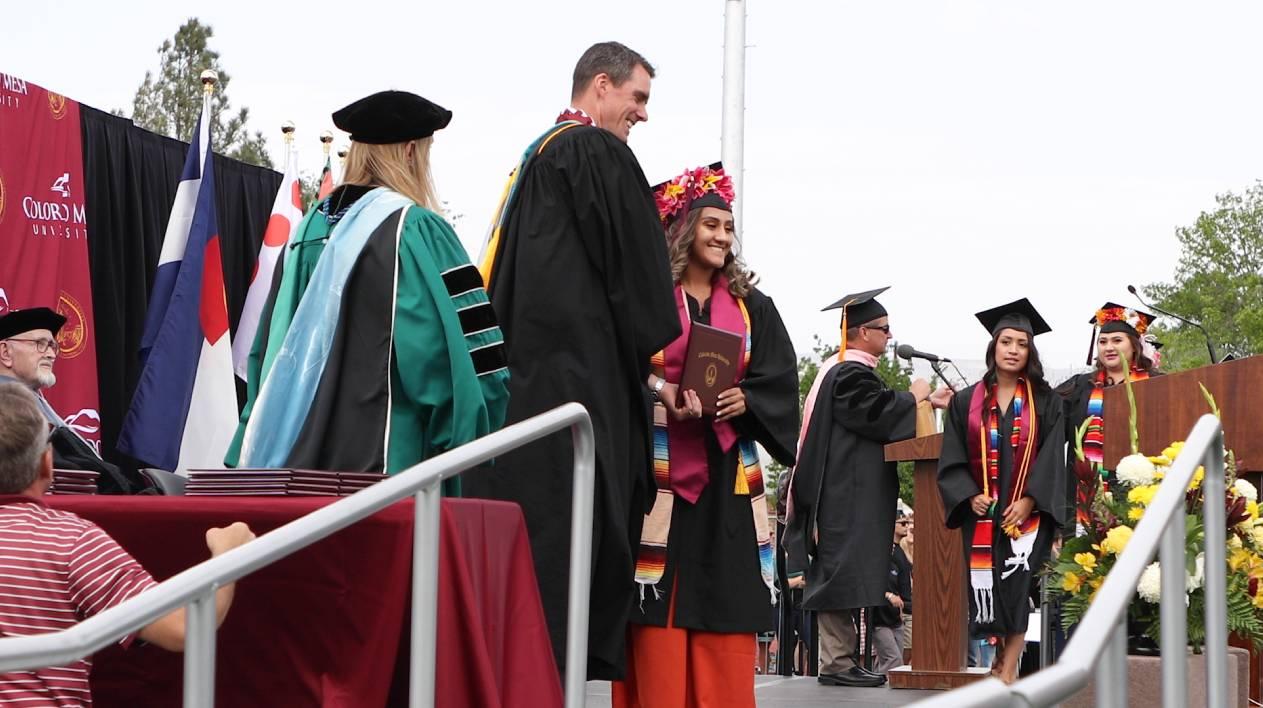 graduates claiming diploma on stage