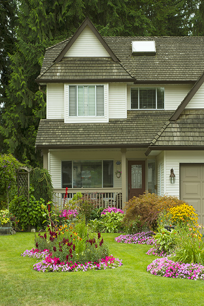 A beautiful Home and manicured yard with a garden full of perennials and annuals.