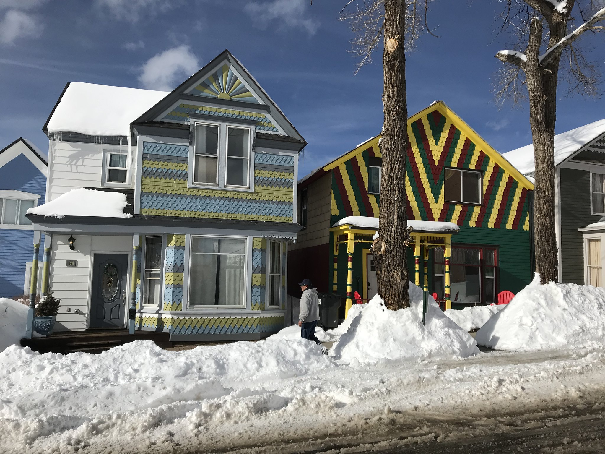 Two colourful houses on a snowy street