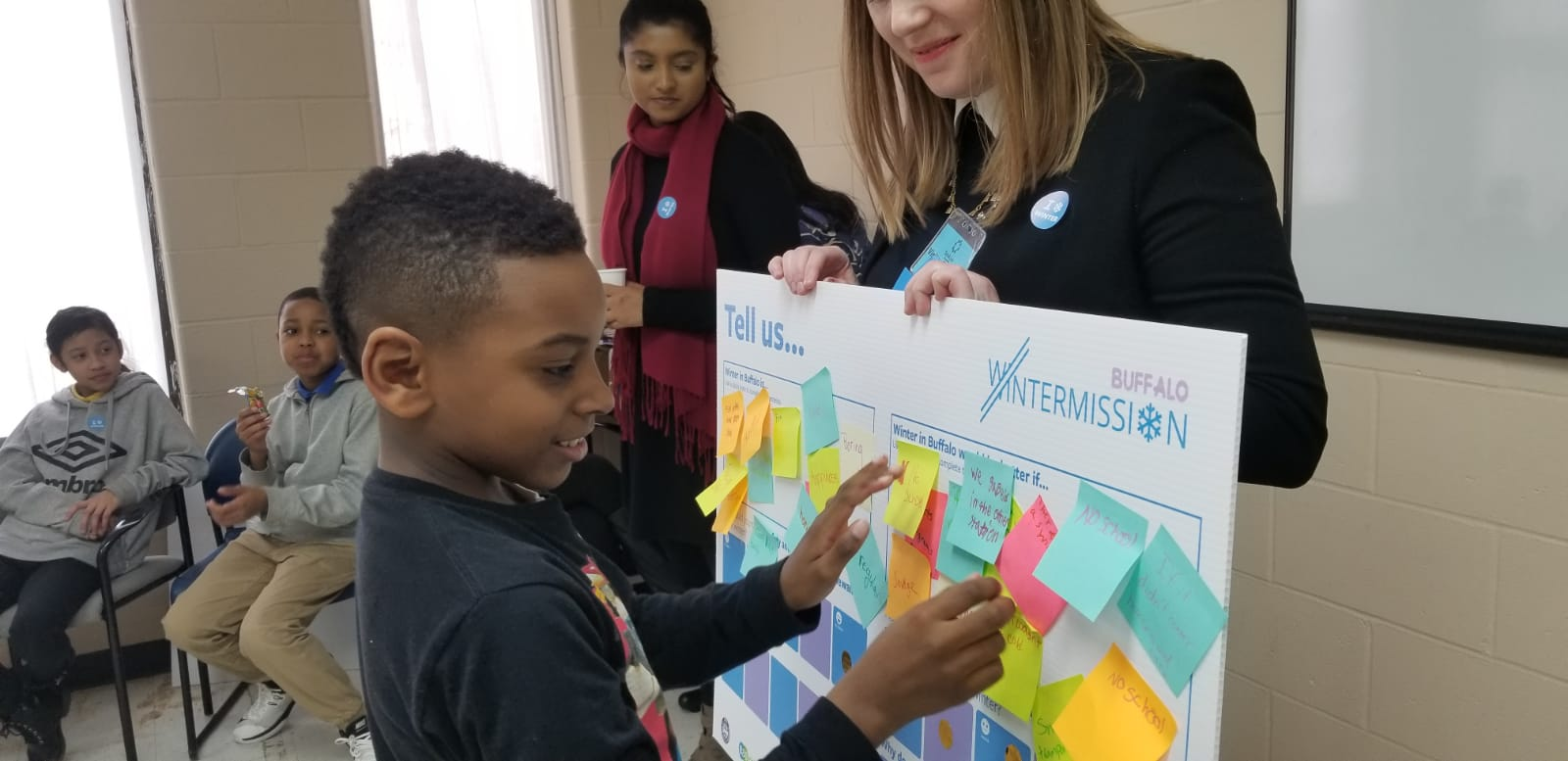 A boy attaching a post it note to a poster board