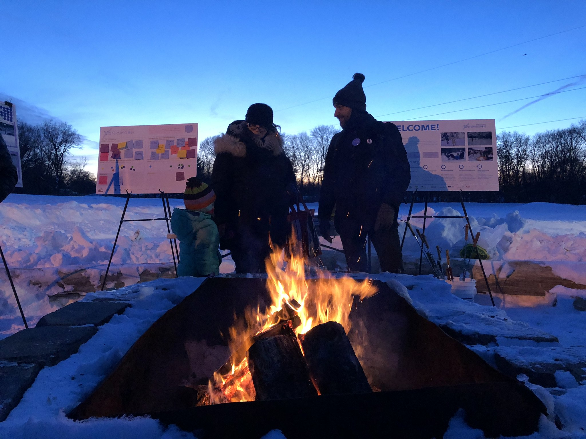 Two adults and a child enjoying an outdoor fire in a snowy location