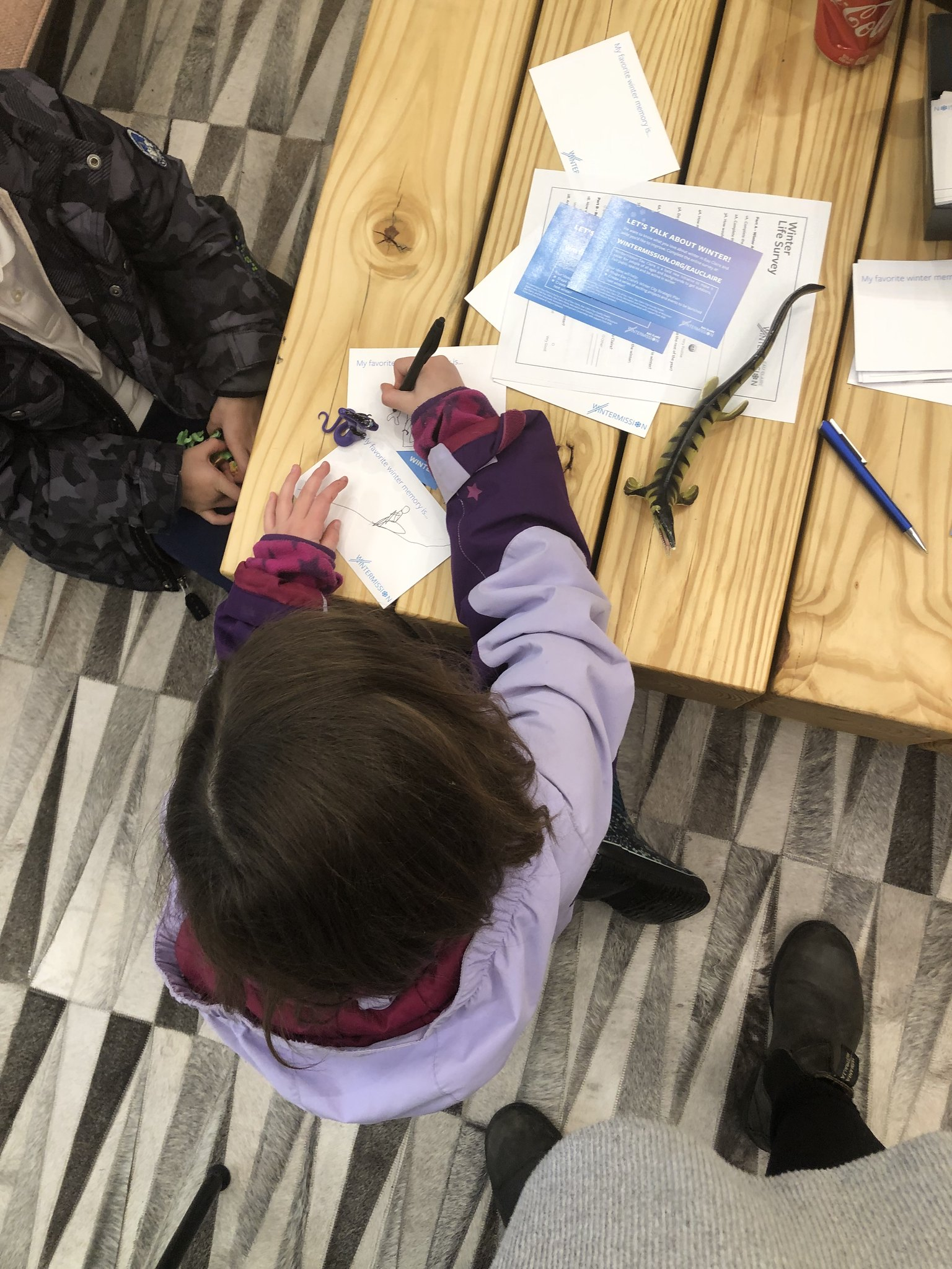 A child writing on a piece of paper citing at a table