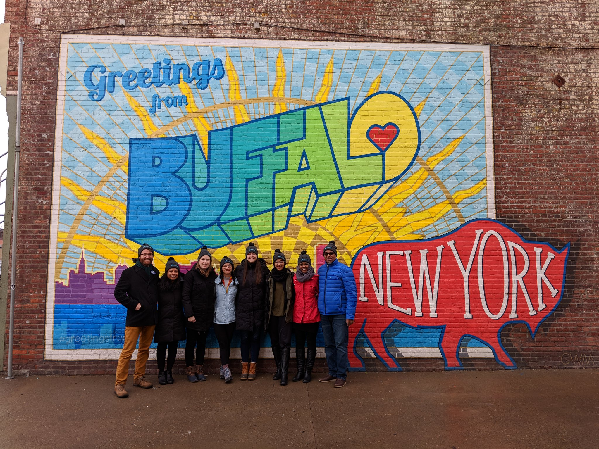 A large colourful mural reading Greetings from Buffalo New York; a group posing in front of the mural