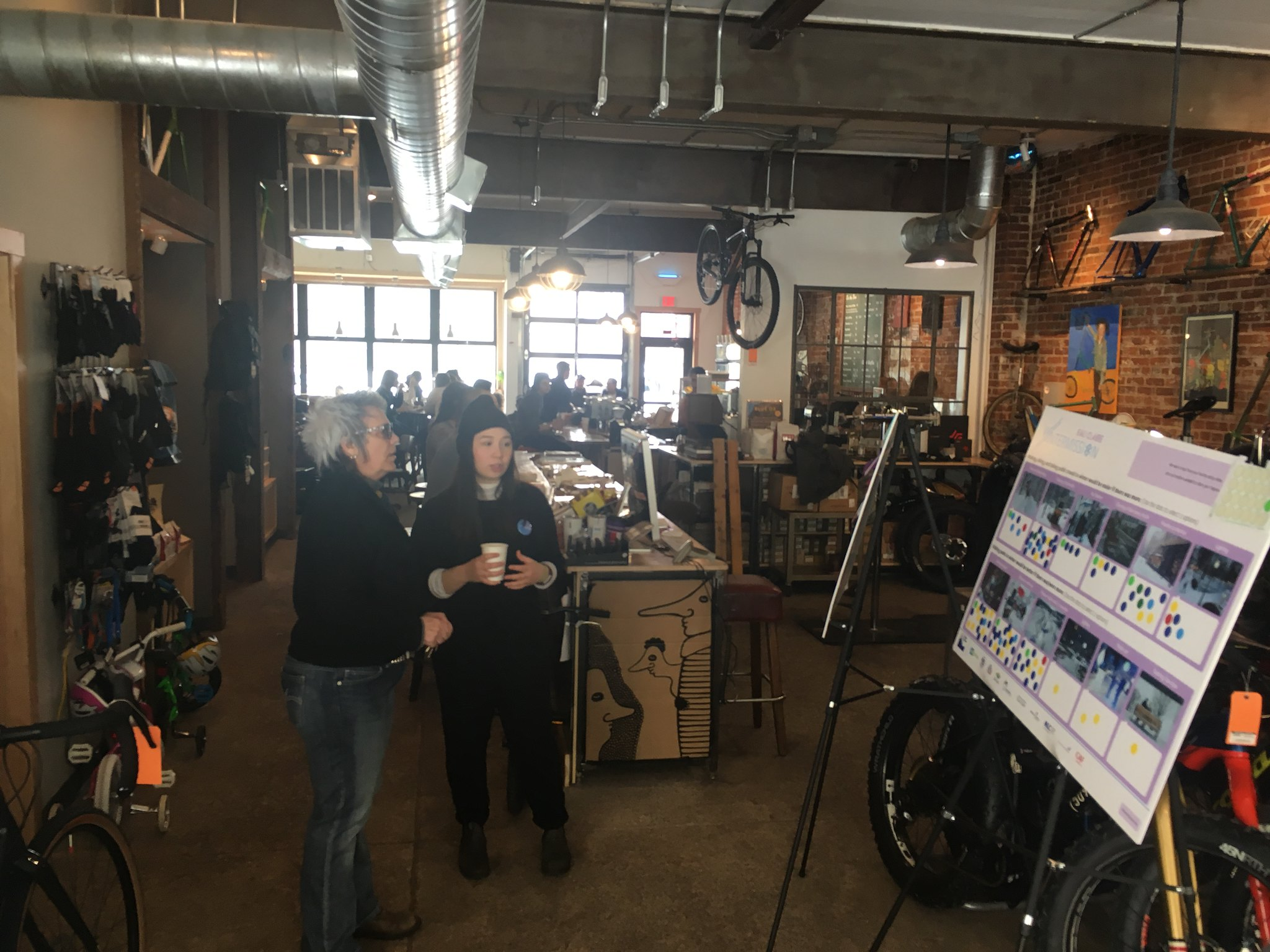Twopeople in a bike shop looking at a poster board