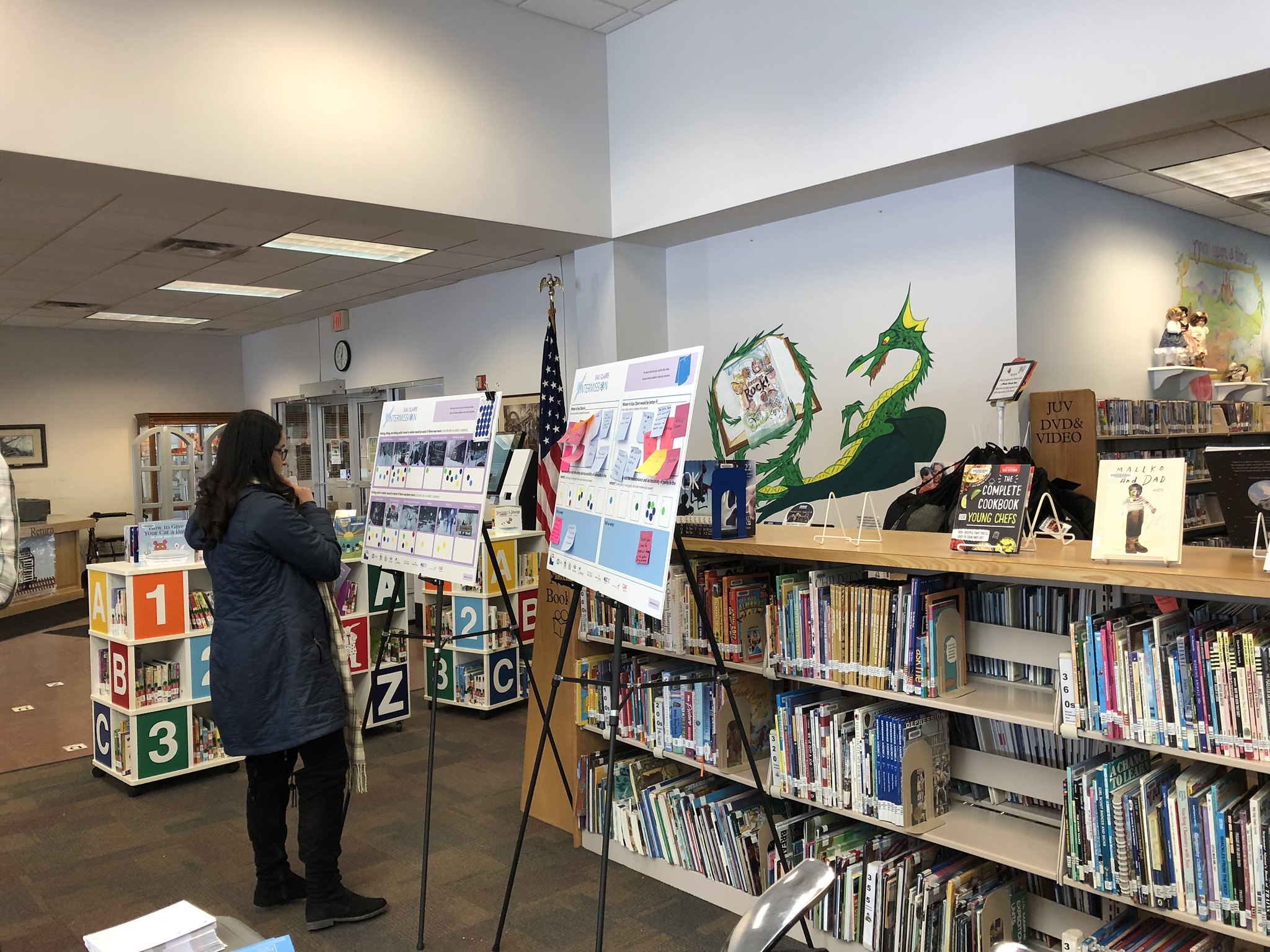 A woman looking at a poster board in a book shop or library