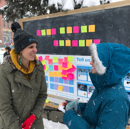 Two women smiling in front of an outdoor bulletin board with colourful notes on it