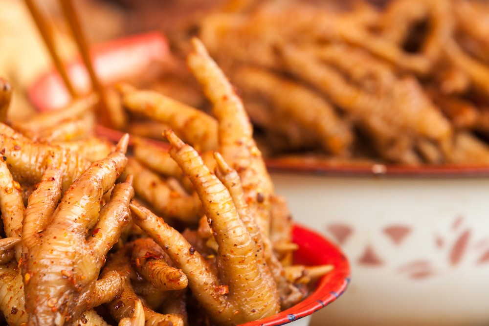 Chicken feet waiting to be eaten at the market in Xinjie, China.