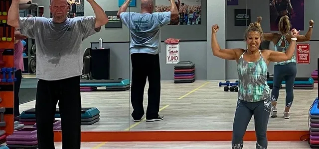An old man and a woman working out