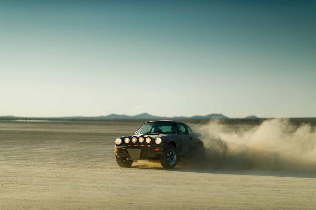Custom Built 1987 Porsche 911 Carrera in Cassis Red with European bus fabric interior spinning dirt in the desert