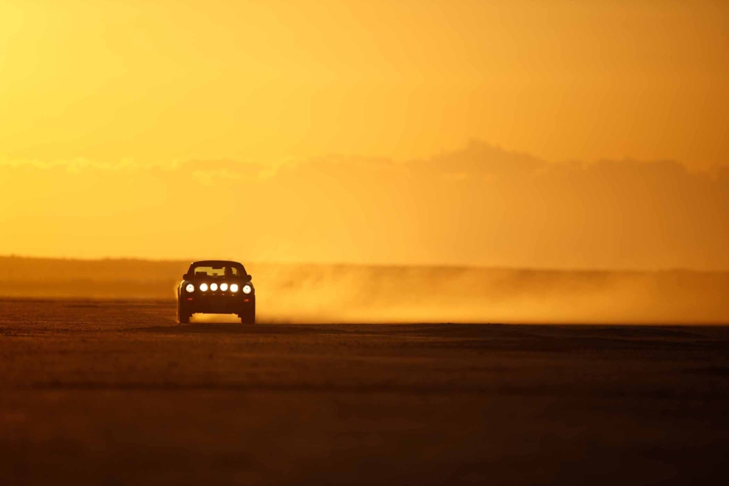 Custom Built 1987 Porsche 911 Carrera in Cassis Red with European bus fabric interior driving through the desert at sunset