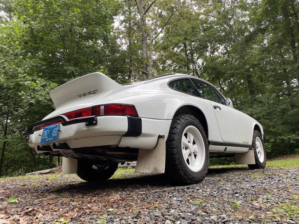 3/4 rear view of a Custom Built 1981 Porsche 911 SC with Grand Prix White exterior and Cow Interior parked in the woods