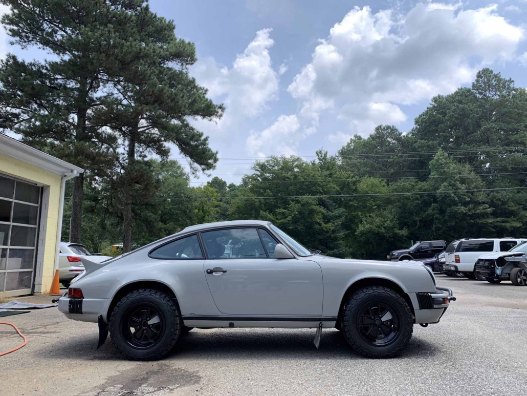 side view of a rear view of a custom 1986 Porsche 911 Carrera with Chalk exterior color and Porsche Pepita interior parked in front of a garage