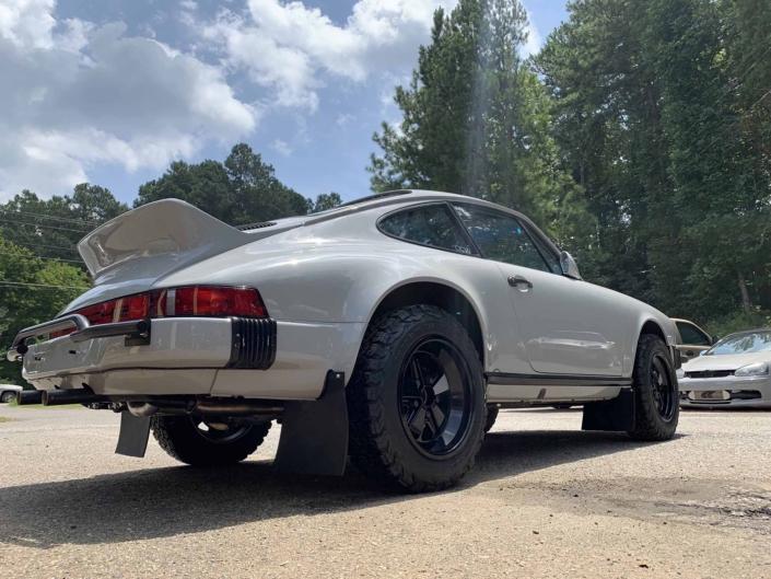 3/4 rear view of a rear view of a custom 1986 Porsche 911 Carrera with Chalk exterior color and Porsche Pepita interior