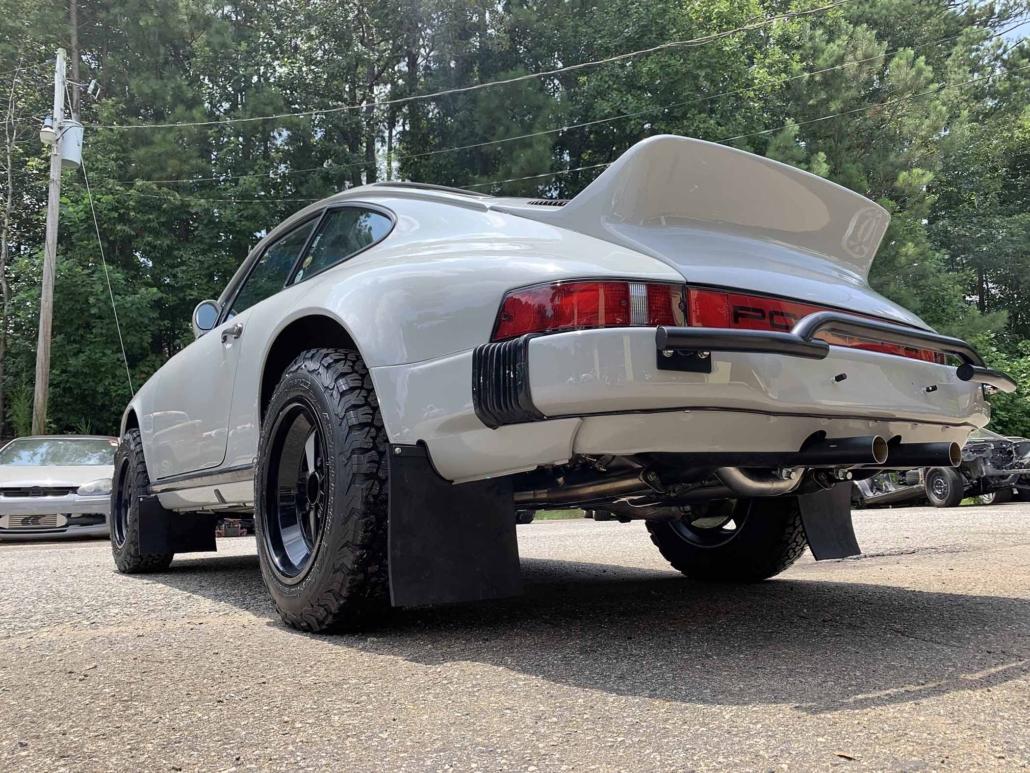 rear view of a rear view of a custom 1986 Porsche 911 Carrera with Chalk exterior color and Porsche Pepita interior