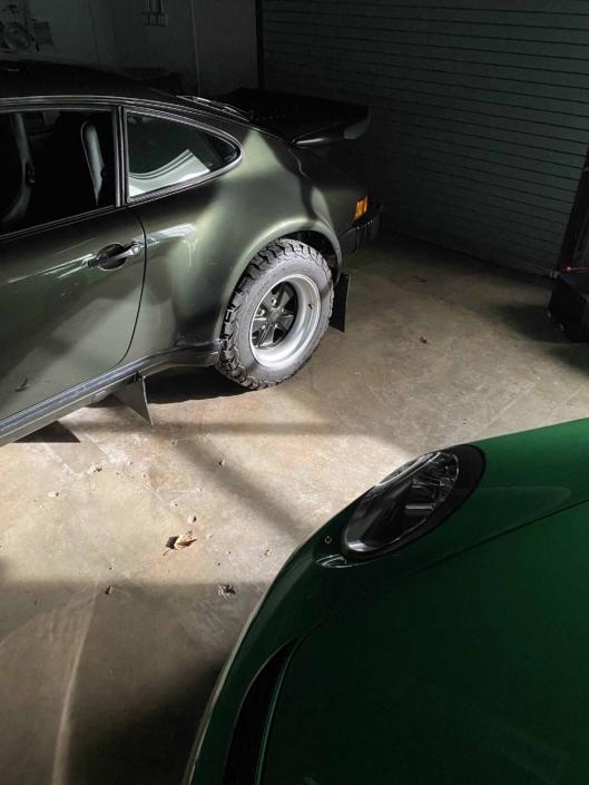 Custom Built 1986 Porsche 930 Turbo with Oak Green Metallic Exterior and Porsche tartan interior parked inside a garage