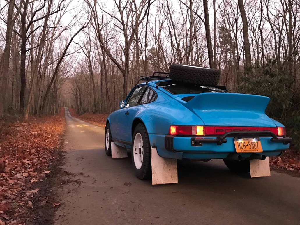 rear 3/4 view of a Custom Built 1980 Porsche 911 SC in Riviera Blue driving through the woods at dusk