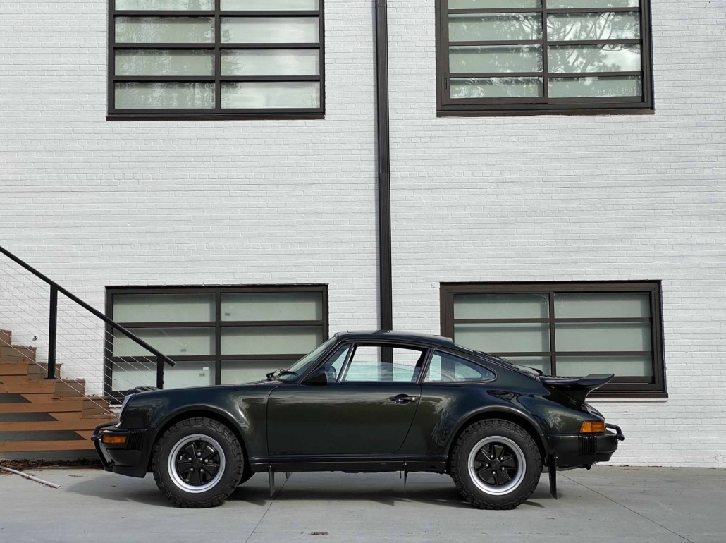 side view of a Custom Built 1986 Porsche 930 Turbo with Oak Green Metallic Exterior and Porsche tartan interior parked in front of a house