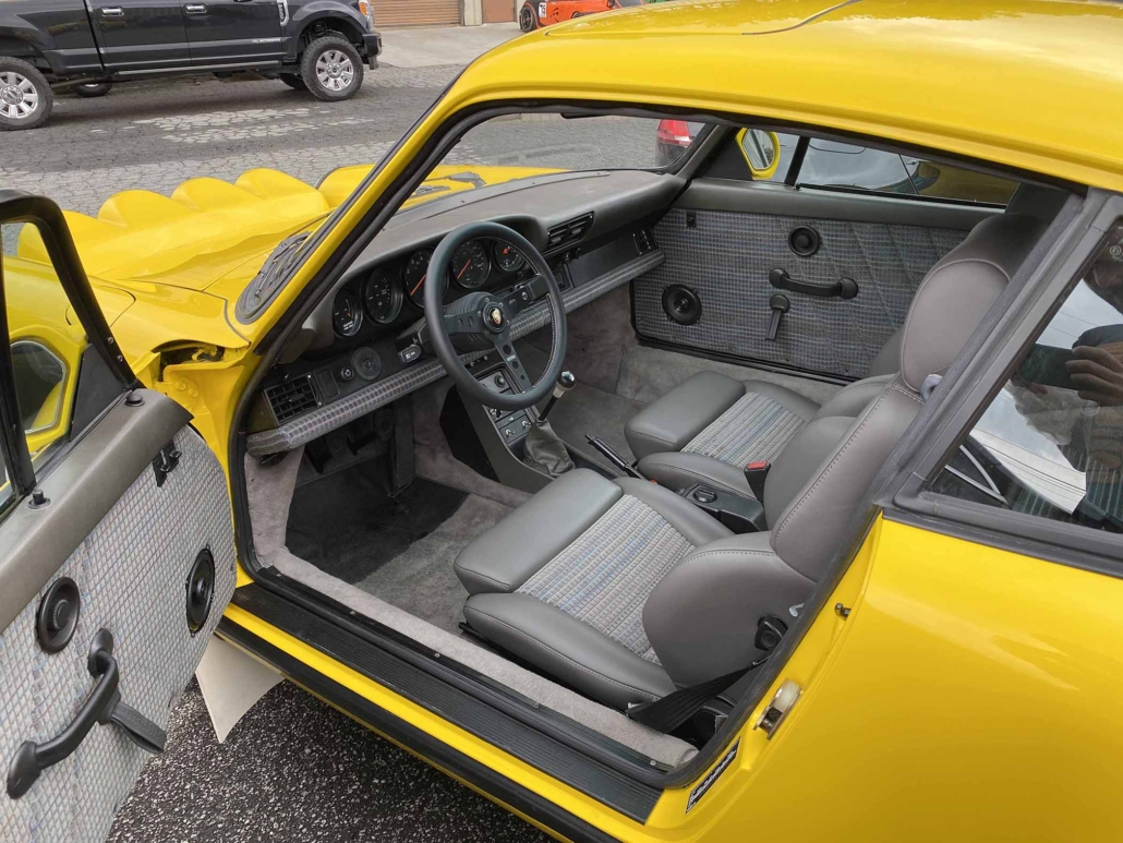 Custom Built 1988 Porsche 911 Carrera with Cadmium Yellow exterior and Opel fabric interior with the door open showcasing the front interior