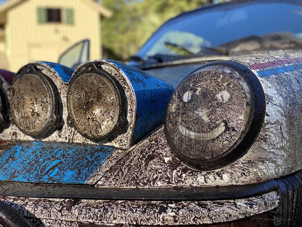 muddy headlight of a Custom Built 1982 Porsche 911 SC with Brumos Livery Exterior and Porsche Tartan Interior