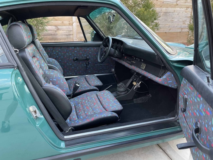 Custom Built 1974 Porsche 911 in Smyrna Green with Fiat fabric with the door open showcasing the custom interior