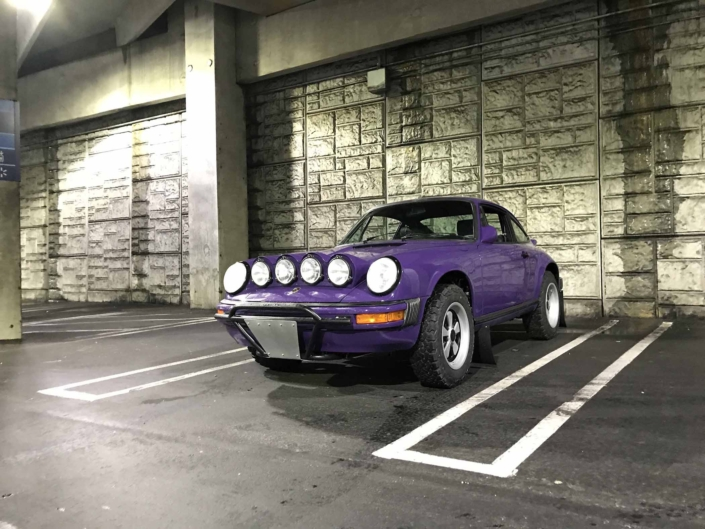 Custom Built 1978 Porsche 911 SC with Lilac exterior and Pascha interior parked in a parking space with the headlights on