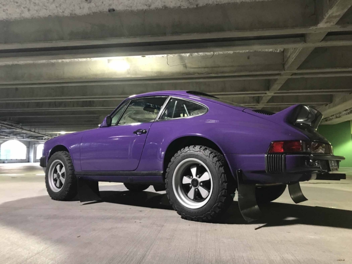 3/4 side view of a Custom Built 1978 Porsche 911 SC with Lilac exterior and Pascha interior in a parking garage