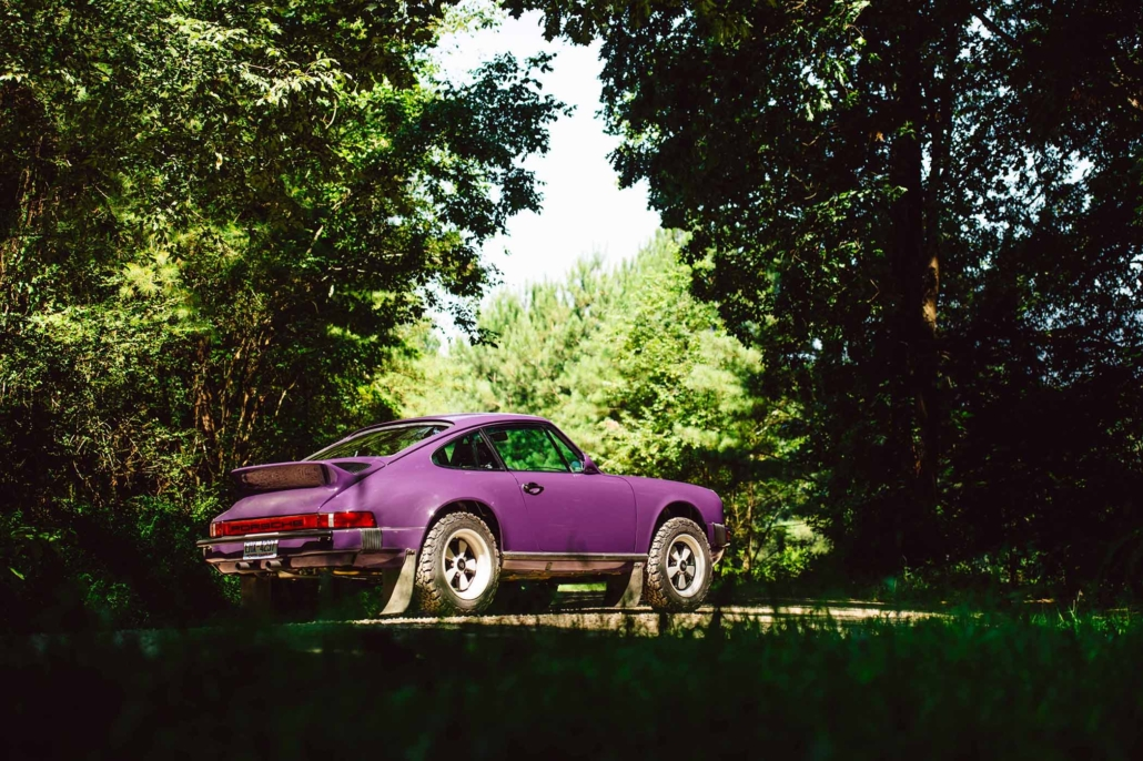 3/4 side view of a Custom Built 1978 Porsche 911 SC with Lilac exterior and Pascha interior in the woods