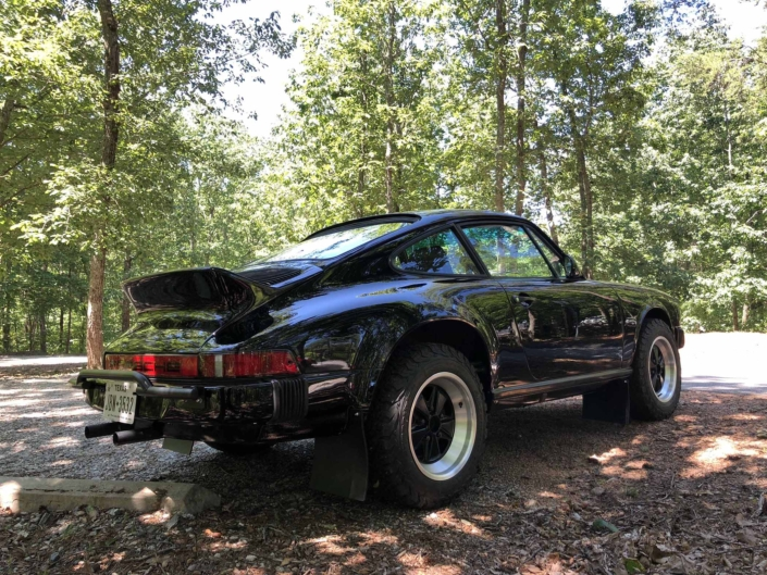 rear view of a Custom Built 1986 Porsche 911 Carrera with Shwartz Exterior and Mercedes G Fabric Interior parked in the woods