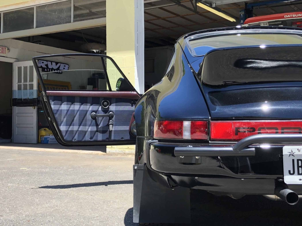 Custom Built 1986 Porsche 911 Carrera with Shwartz Exterior and Mercedes G Fabric Interior with the door open showcasing custom interior design