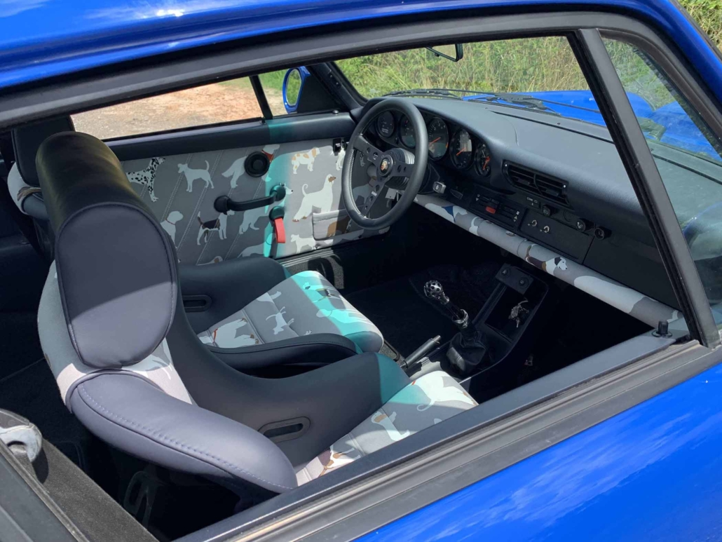 open window on a Custom Built 1988 Porsche 911 Carrera in Acid Blue with Dog fabric interior showcasing the front seating