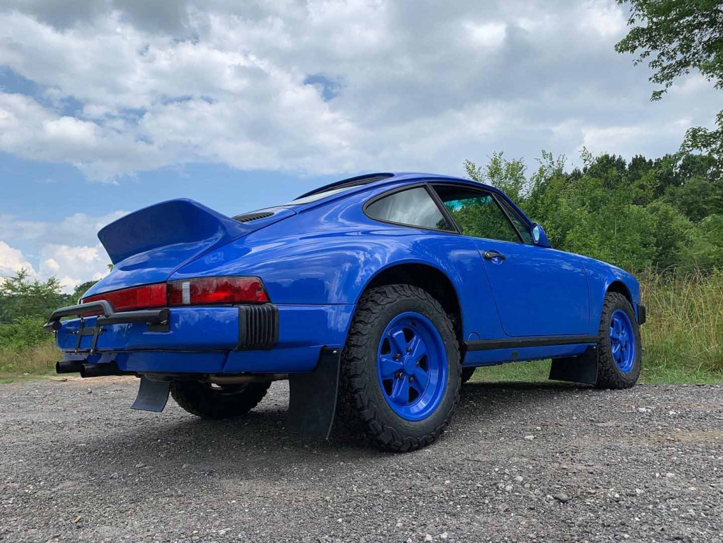 3/4 view of a Custom Built 1988 Porsche 911 Carrera in Acid Blue with Dog fabric interior with the window down