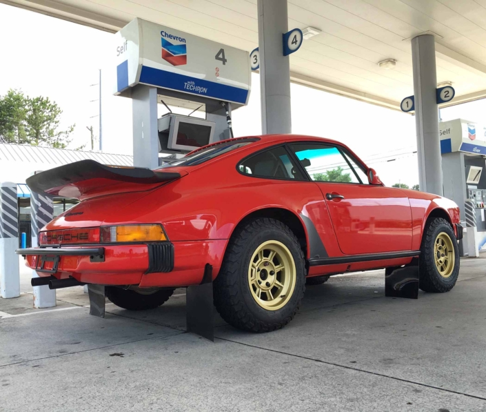 Custom Built 1986 Porsche 911 Carrera in Indian Red with Porsche Studiocheck Interior parked at a gas station