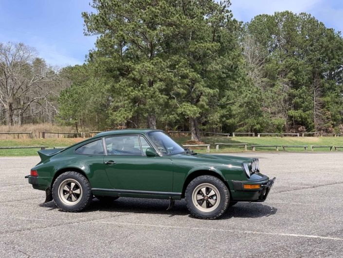 Custom built 1982 Porsche 911 SC in Irish Green with VW tartan interior parked in a parking lot
