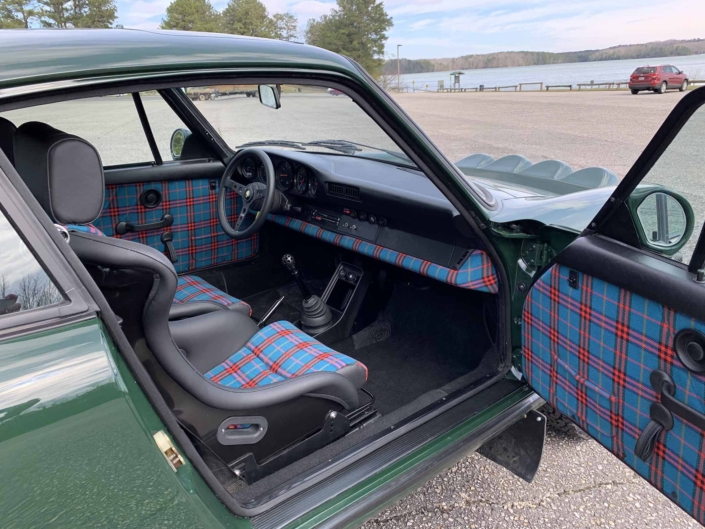 Custom built 1982 Porsche 911 SC in Irish Green with VW tartan interior parked with the door open