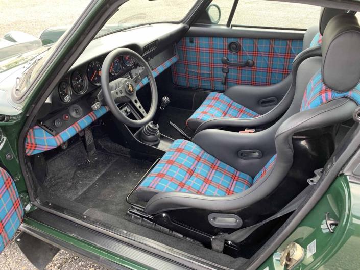 Custom built 1982 Porsche 911 SC in Irish Green with VW tartan interior parked with the door open showcasing the interior