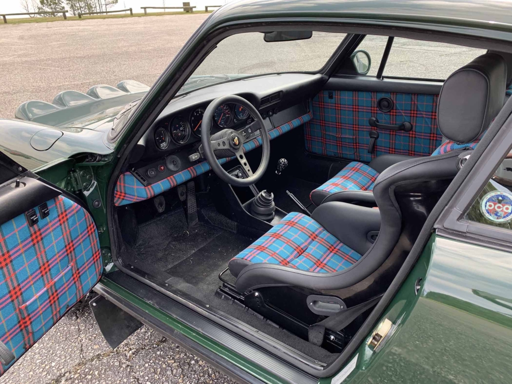 Custom built 1982 Porsche 911 SC in Irish Green with VW tartan interior parked with the door open showcasing the interior
