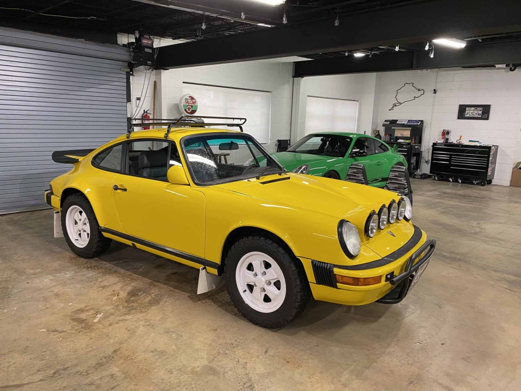 Custom Built 1988 Porsche 911 Carrera with Cadmium Yellow exterior and Opel fabric interior parked in a garage