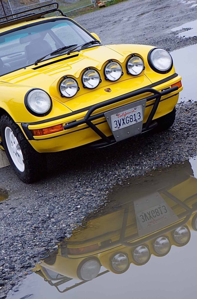 headlight shot of a Custom Built 1988 Porsche 911 Carrera with Cadmium Yellow exterior and Opel fabric interior parked in front of a puddle