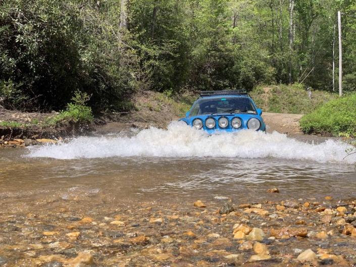 3/4 view of a Custom Built 1980 Porsche 911 SC in Riviera Blue driving through water