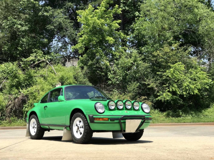 Custom Built 1981 Porsche 911 SC in Signal Green with Porsche Tartan Interior parked on the dirt with the woods in the background