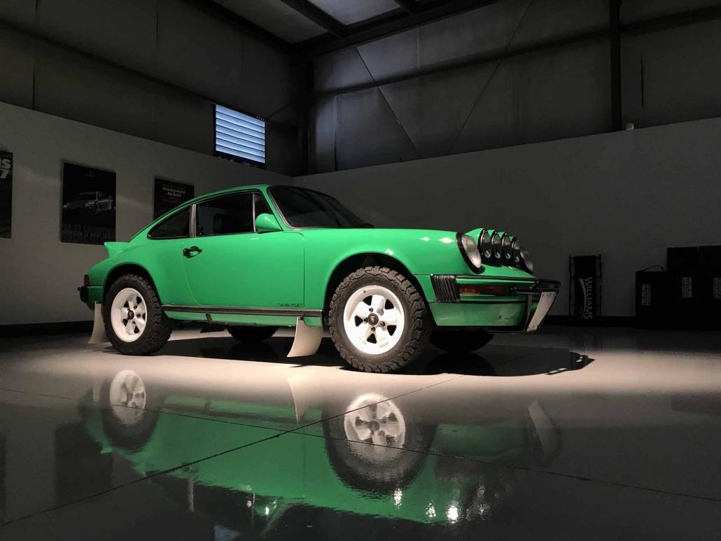 Custom Built 1981 Porsche 911 SC in Signal Green with Porsche Tartan Interior parked in a garage with dramatic lighting