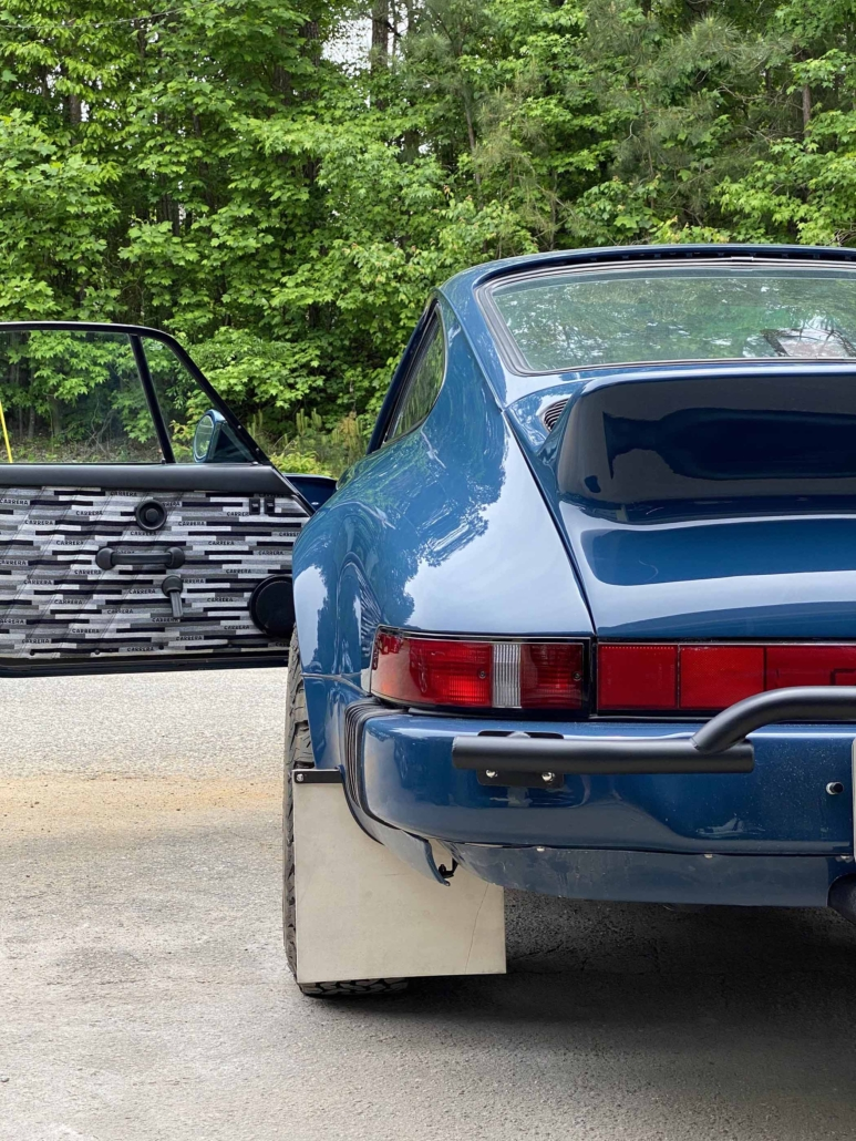 rear view of a Custom Built 1987 Porsche 911 Carrera with Aga Blue exterior and Carrera fabric interior with the door open