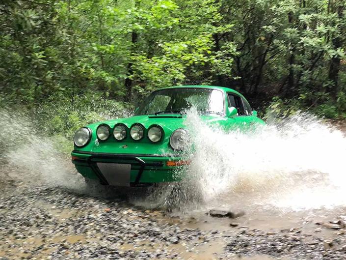 Leh Keen's Custom Built 1981 Porsche 911 SC in Signal Green with Porsche Tartan Interior driving through water in the woods