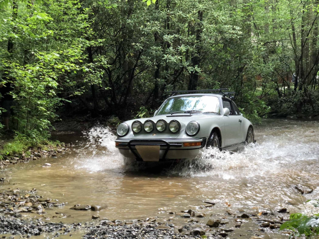 Custom Built 1986 Porsche 911 Carrera with Fashion Grey Exterior and Lancia Fabric Interior driving through the water in the woods